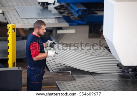Inside a factory, industrial worker in action on metal press machine holding a piece of steel ready to be worked.