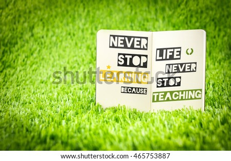 Inspiration quote, Never stop learning because life never stop teaching word on book on green greass ,Motivational typographic