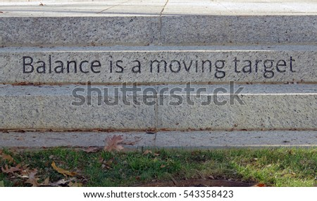 "Inspirational engraving in a staircase that reads ""Balance is a moving target."""