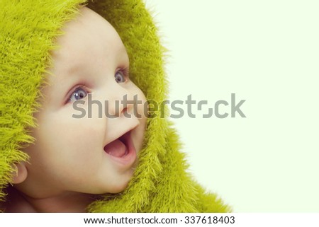 Instagram style photograph of beautiful smiling baby wrapped in a furry green blanket
