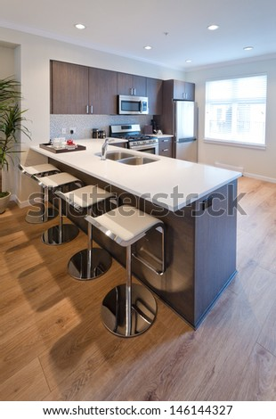 Interior design of a luxury modern kitchen with some sits at the island counter. Vertical.