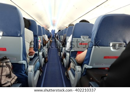 Interior of airplane with passengers on seats waiting to take off.