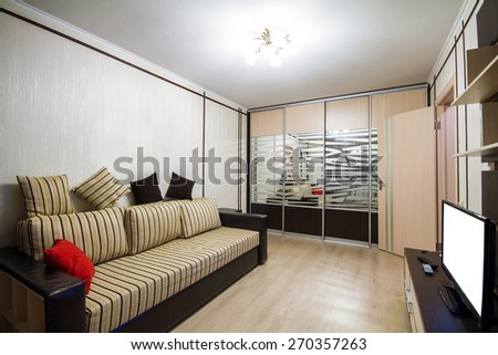 Interior room is equipped with furniture with sofa and TV
