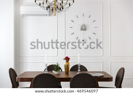 interior room studio apartment with white walls, a kitchen table and a big clock on a wall in a modern style.