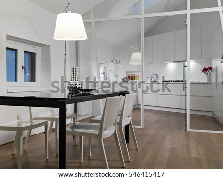 interior view of a modern living room in foreground the dining table overlooking on the kitchen whose floor is made of wood