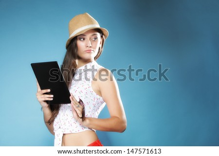 Internet modern lifestyle concept. Young summer girl in hat using tablet computer reading. Latin female with e-book reader touchpad pc.
