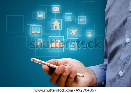 Internet of things (IOT) concept. Businessman holding smart phone and wireless communication network, represented by symbol connected with icons of typical.