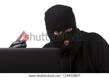 Internet Theft - a man wearing a balaclava sat behind a laptop holding a credit card, white background.