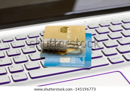 internet transaction security concept   - plastic cads with padlock on laptop keyboard