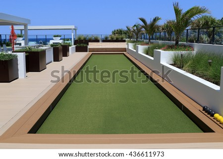 Inviting bocce ball court with artificial turf on a rooftop terrace.