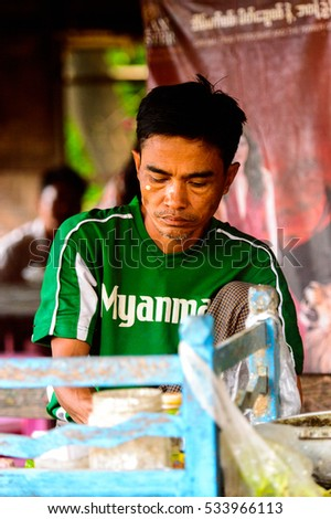 INWA, MYANMAR - AUG 25, 2016: Unidentified Burmese boy in a green shirt. 68 per cent of  Myanma people belong to Bamar ethnic group