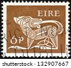IRELAND - CIRCA 1968: A stamp printed in Ireland shows a dog from an ancient artwork, circa 1968. - stock photo
