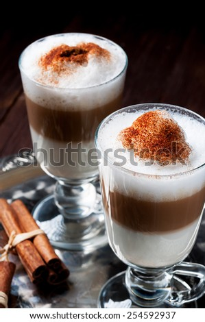 Irish coffee cup filled latte machiato poured layers on the metal tray.Cinnamon sticks.
