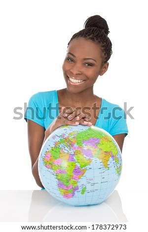 Isolated african american smiling woman sitting with globe in front of her.