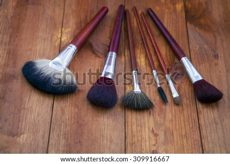 isolated brushes on a wooden background