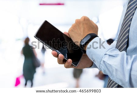 isolated business man with smart wristband and smartphone on on bridge background