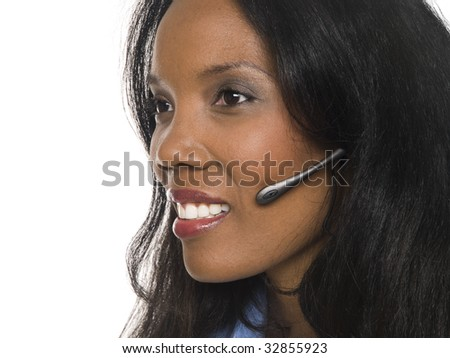 Isolated closeup studio shot of an African American businesswoman talking on a telephone headset.