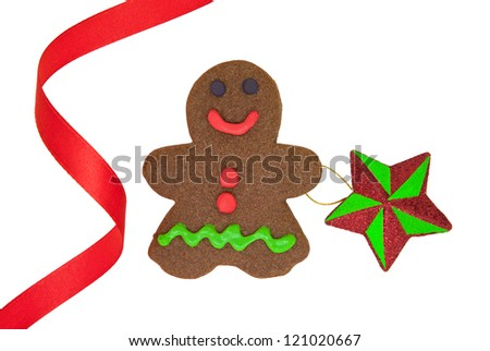 Isolated homemade Gingerbread Man holding a star, decorated with red ribbon.
