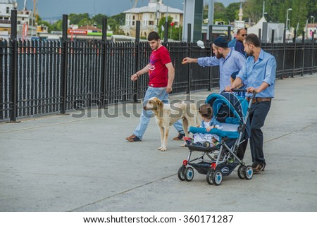 Istanbul, Turkey - May 13, 2014: Public street in Istanbul where a white dog surrounded by bunch of men and child