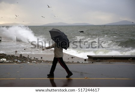 Istanbul, Turkey, 10 November 2016 People  walking on the coast of sea in stormy weather in Istanbul