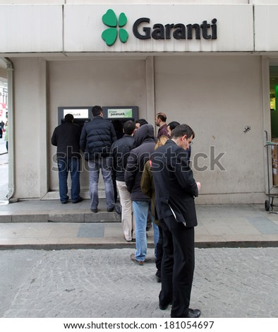 ISTANBUL, TURKEY - SATURDAY, MARCH 8, 2014: Customers wait on line to access money from an ATM machine at a Garanti Bank in Istanbul, Turkey, on Saturday, March 8, 2014.
