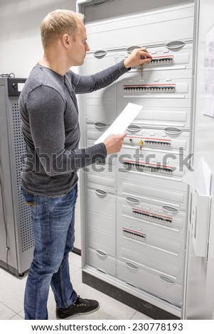 IT engineer works in large fuse cabinet