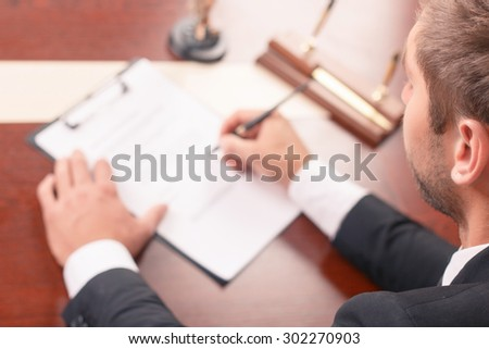 It is my job. Top view of positive lawyer sitting at the table and holding pen while signing documents.
