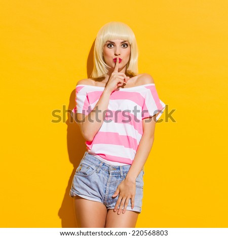 It's a secret. Beautiful blonde young woman holding finger on her lips. Three quarter length studio shot on yellow background.