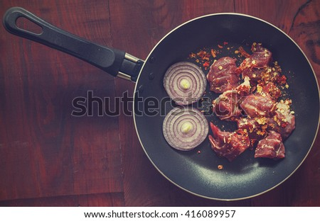 Italian Cuisine. Raw meat with spices in a pan, hot chili peppers, cherry tomatoes, rosemary on a wooden table background. Flat location, closeup.