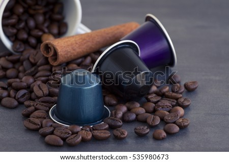 Italian espresso coffee capsules or coffee pods on a dark stone or marble  background with some roasted coffee beans