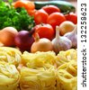 Italian pasta and fresh vegetables on the kitchen table. - stock photo