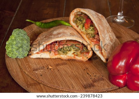 italian pizza calzone on a wooden plate