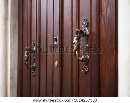 Italian Wooden Door. Artistic Handles Representing Mermaids.