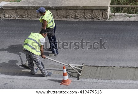 Italy, Sicily; 12 May 2016, men at work fixing a road - EDITORIAL