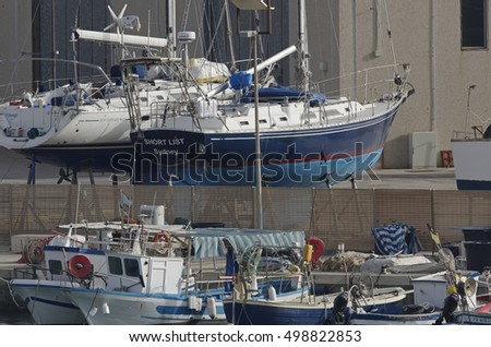 Italy, Sicily, Mediterranean sea, Marina di Ragusa; 15 October 2016, wooden fishing boats and luxury yachts ashore in a boatyard in the port - EDITORIAL