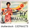 JAMAICA - CIRCA 1972: Stamp printed in Jamaica shows A Flight Attendant Standing In Front Of An Air Jamaica Airplane, circa 1972 - stock photo