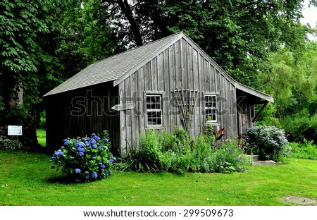 Jamestown, Rhode Island - July 18, 2015:  Wooden Caretaker's Cottage with blue Hydrangeas at the 1796 Watson Farm on Conanicut Island