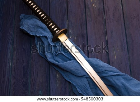 japan katana sword on the wood background with the blue shawl