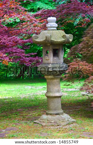 Japanese lantern in stroll garden with decorative background trees.