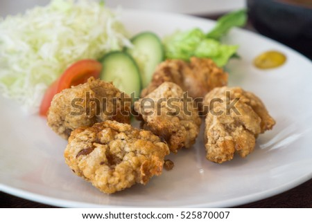 Japanese style deep fried chicken, crispy fried chicken in white plate with cabbage, cucumber and tomato for salad
