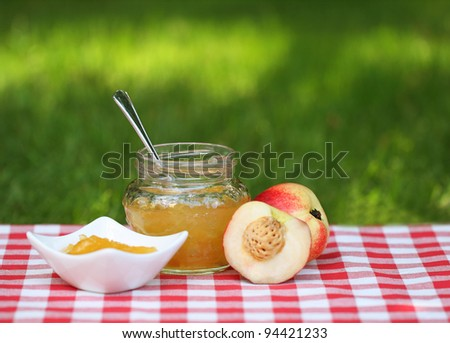 Jar of peach jam and some peaches on the napkin