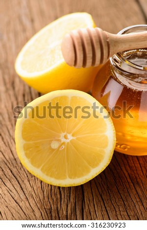 Jars of honey with lemons on wooden table