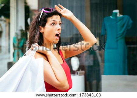 Jaw dropping woman looking amazed about shopping dress sales.