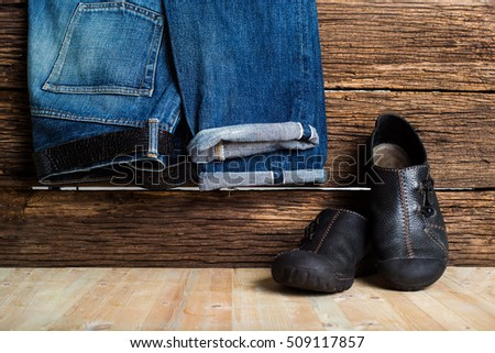 Jeans and jacket. draped placed with black leather shoes. On the ground of old wood. Retro style