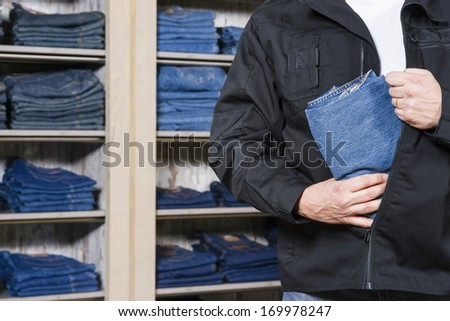 jeans being stolen by a shoplifter in a shop