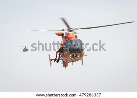 JERSEY CITY NJ MAY 29 2016: U.S. Coast Guard rescue swimmer hangs from a line on the orange MH-65 Dolphin helicopter during a Search and Rescue demonstration at Liberty State Park at Fleet Week 2016.
