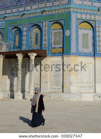 JERUSALEM - FEBRUARY 20: A woman passes the Dome of the Rock on the Temple Mount February 20, 2012 in jerusalem, Israel. Among Sunnis, the site is the 3rd holiest in Islam.