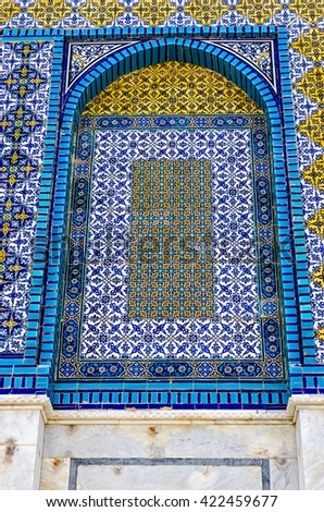 JERUSALEM, ISRAEL JUNE 10 2015: Closeup view of the intricate, colorful, geometric, mosaic ceramic tiles of the Dome of the Rock in Jerusalem.  The tiles have blue, green, yellow and white colors.