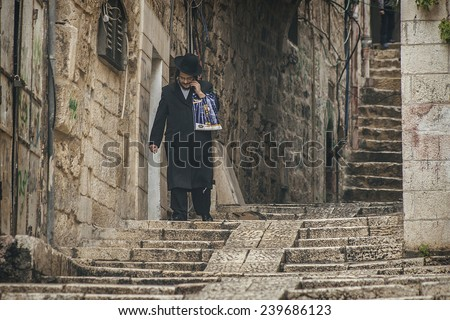 JERUSALEM - MAY 17: A Hasidic Jewish man wears a fur hat and bekishe along a walkway in the Old City of Jerusalem March 17, 2014 in Jerusalem