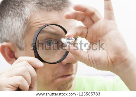 Jeweler looking intrigued at a diamond